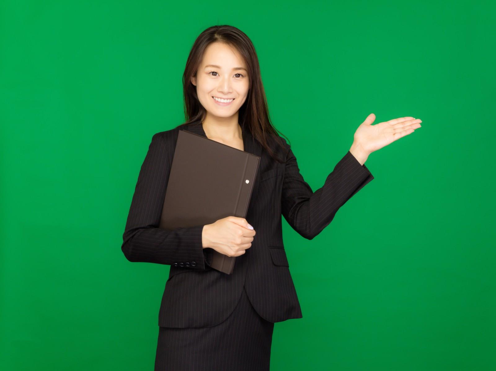 資料をもって案内するスーツ姿の女性(グリーンバック)のフリー画像(写真) モデル:土本寛子