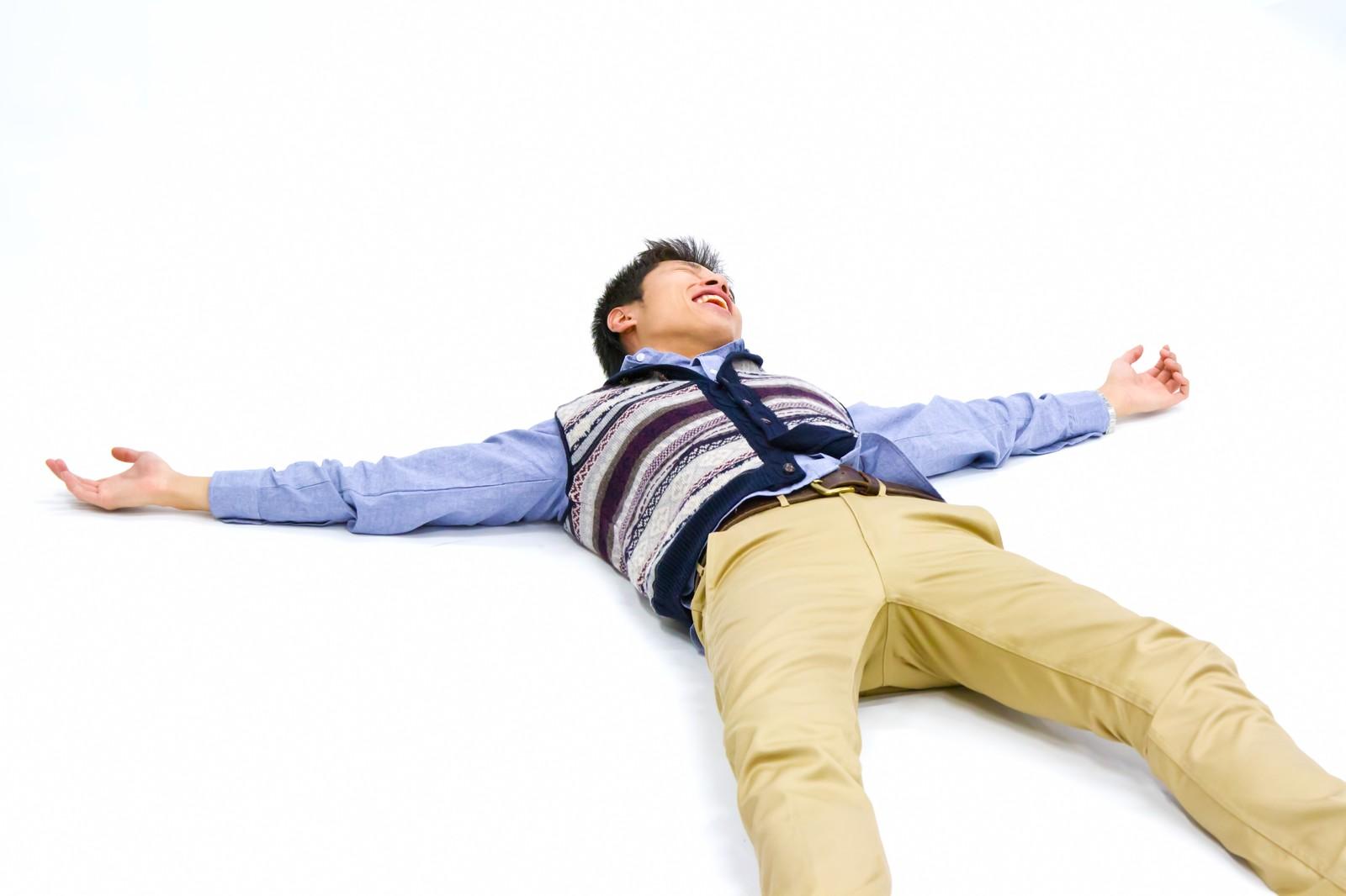 仰向けに寝て両手を広げる男性 [モデル:恭平]