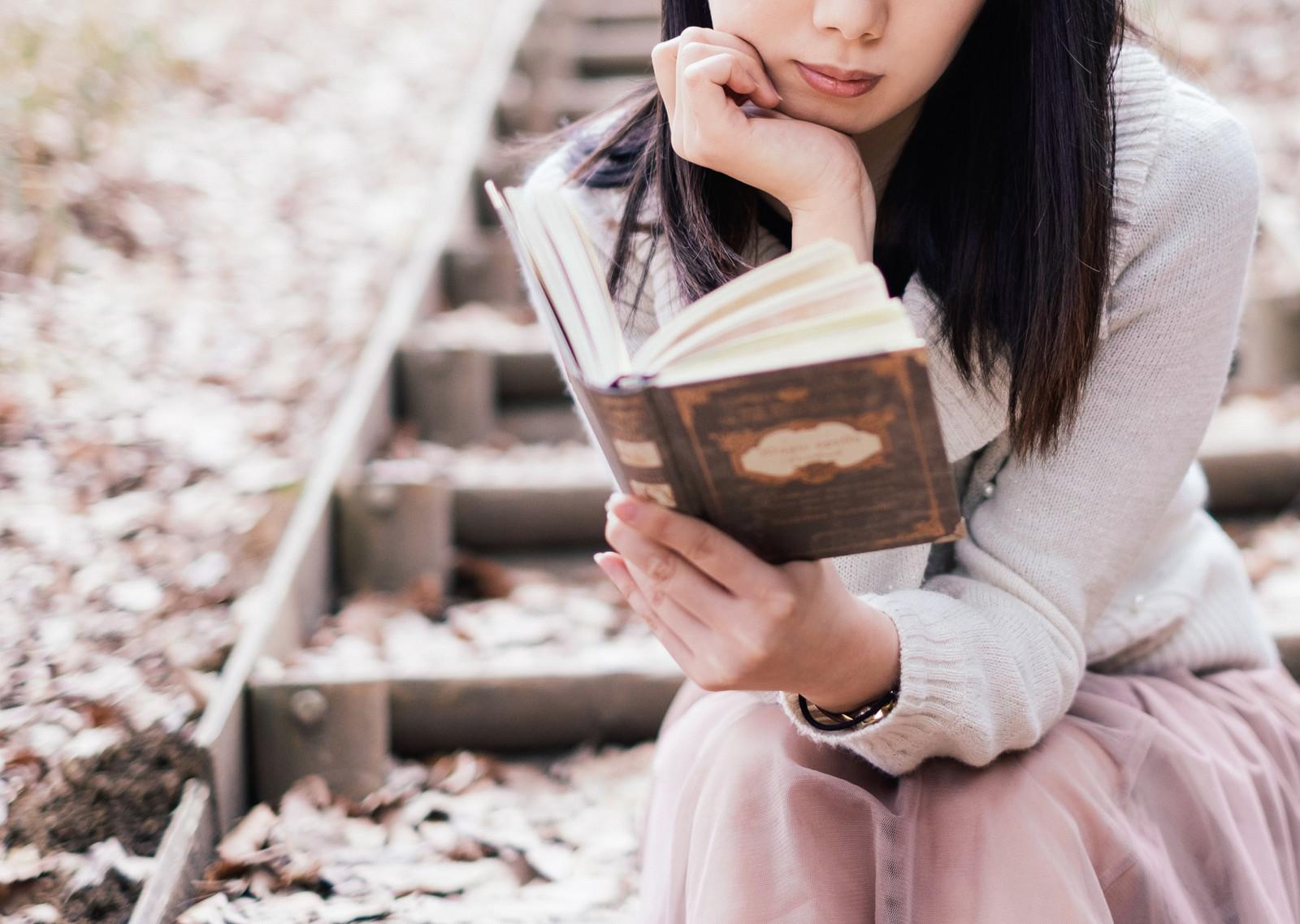 屋外で洋書を読む女性のフリー画像(写真)